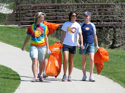 residents carrying trash bags after cleanup event
