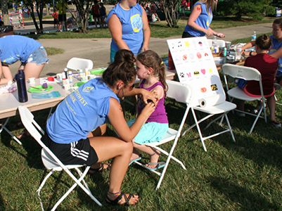 Volunteer painting childs face at All-City Play Day