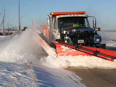 truck plowing snow on city street