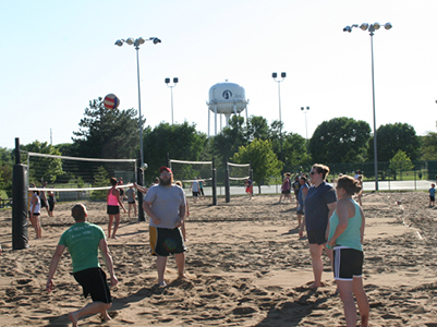 Adults playing sand volleyball