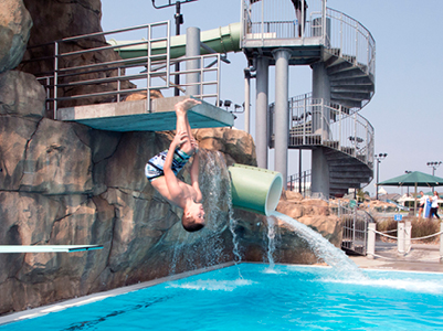 boy flipping off diving board at Cascade Falls Aquatic Center