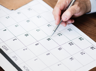 hand with pencil pointing at calendar
