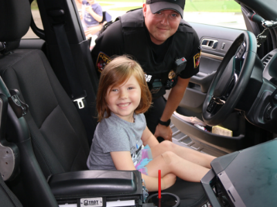 young girl in police car with officer