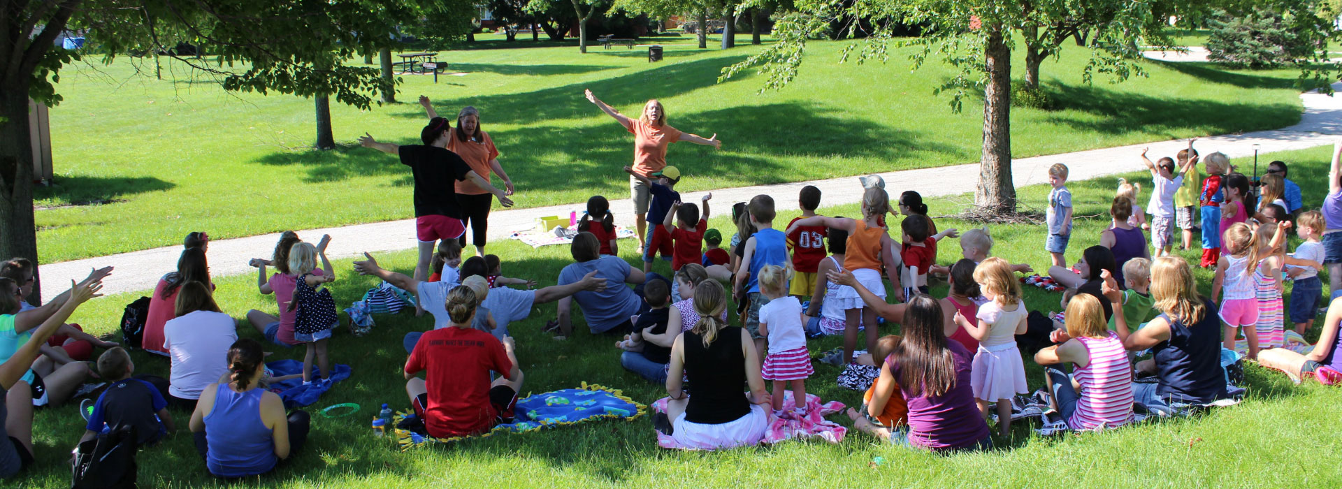 library-story-time-in-the-park-two-librarians-reading-to-crowd