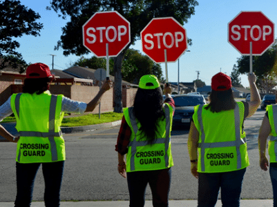 several crossing guards  holding stop signs